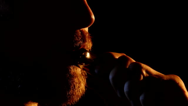 Guy exhales smoke into a dark room. Black background. Close up video