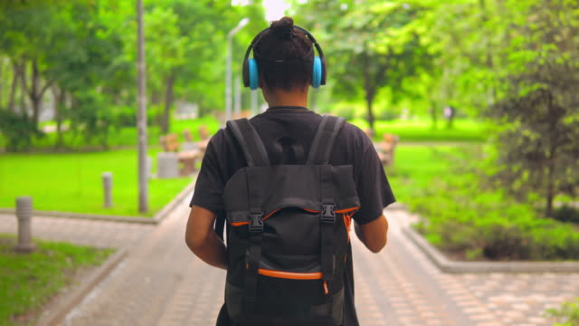 guy going and dancing in city park back view funny man with backpack walking on the street listening music using headphones natural parkland stock videos & royalty-free footage
