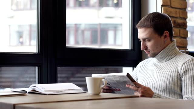 парень в кафе читает газету и пьет кофе - кофе брейк стоковые видео и кадры b-roll