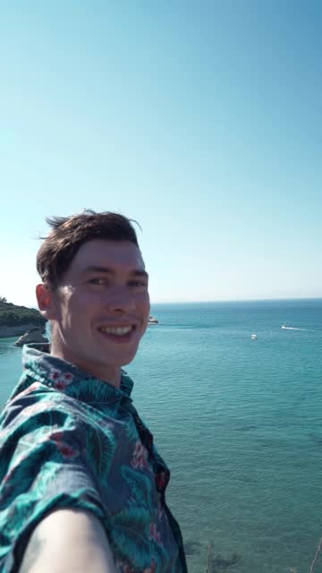 vídeos de stock e filmes b-roll de guy in hawaiian shirt gets a selfie or video call during his vacation at sea. vertical video 9:16 - vertical