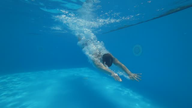 guy in shorts jumps into clean swimming-pool and swims under water in slow motion guy in shorts jumps into clean swimming-pool and swims under water in slow motion dive into the pool on summer weekends diving to the ground stock videos & royalty-free footage