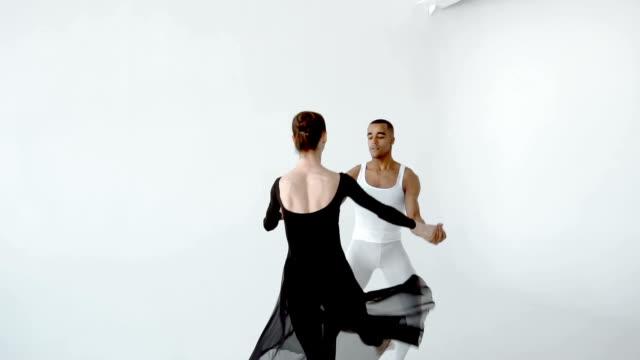 kille i vitt och flicka i svart gör balett i vit dance studio slow motion 120fps. - piruett bildbanksvideor och videomaterial från bakom kulisserna