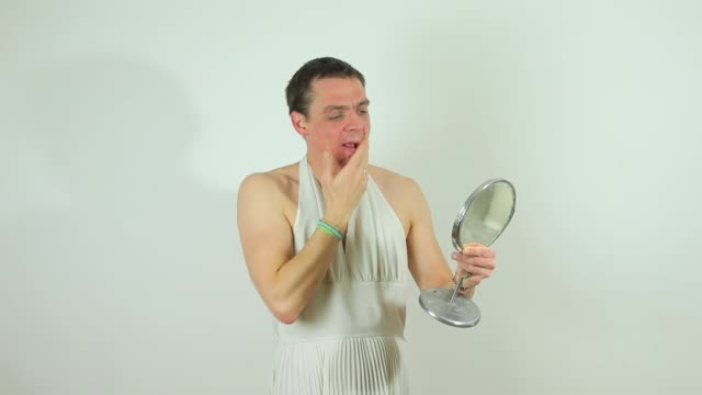 guy in white dress looks in mirror, shows tongue video