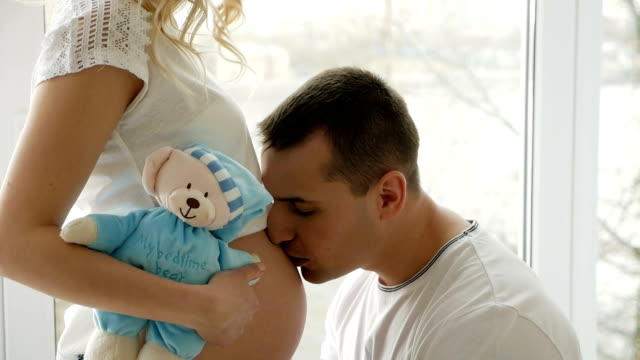 Guy embrasse le ventre de sa femme blonde enceinte debout - Vidéo
