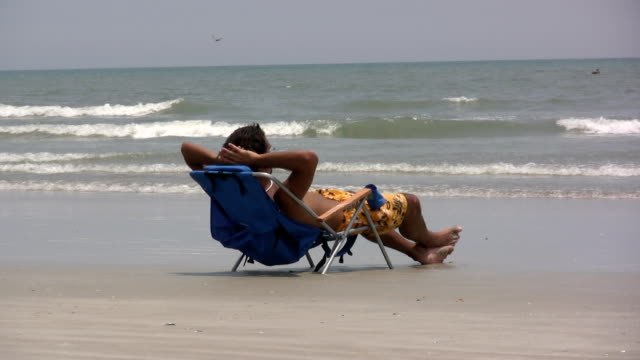 Guy laying in beach chair video