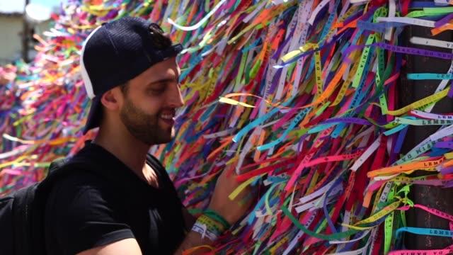 サルバドール、バイーア州、ブラジルのブラジル リボン (fita はボンフィン) 教会の願いを作る男フェンスします。 - 幸運点の映像素材/bロール