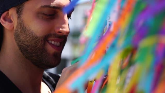 mann macht einen wunsch mit brasilianischen bändern (fita do bonfim) auf kirche zaun in salvador, bahia, brasilien - religion stock-videos und b-roll-filmmaterial
