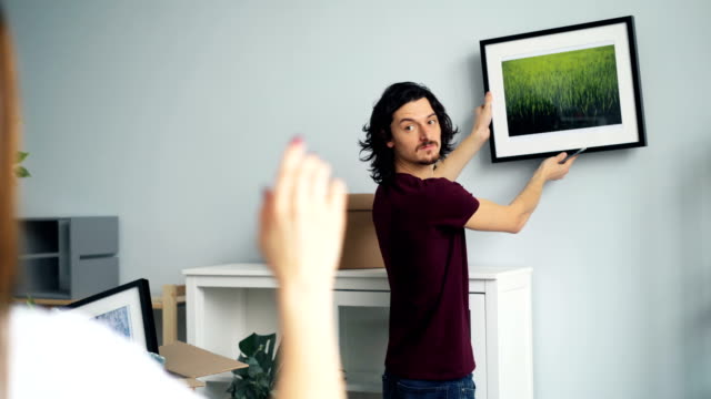 Guy picking place for picture when girlfriend making frame with fingers Handsome guy is picking place on wall to hang modern picture while his girlfriend is making frame with her fingers and gesturing approving his decision. hanging stock videos & royalty-free footage