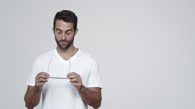 guy putting on glasses - maglietta bianca video stock e b–roll