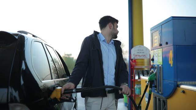 guy refueling car for travel - заправляться стоковые видео и кадры b-roll