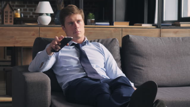 Guy resting in living room. tired man watching tv after hard day. Handsome exhausted businessman relaxing at home handsome people stock videos & royalty-free footage