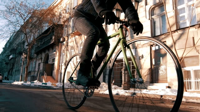 guy riding fixed gear bike in city centre, slow motion - guanto indumento sportivo protettivo video stock e b–roll