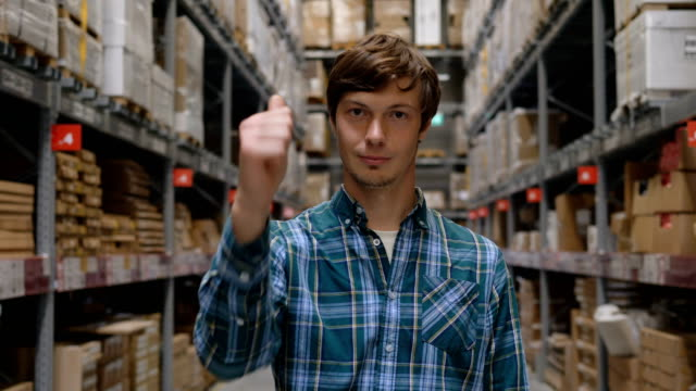 guy shows thumbs-up gesture in storehouse - vídeo