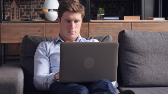 Hombre sentado en el sofá en el piso. - vídeo
