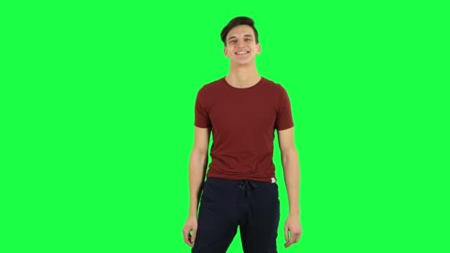 vídeos de stock e filmes b-roll de guy smiling while looking at camera and flirting. green screen - teeshirt template