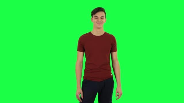 vídeos de stock e filmes b-roll de guy smiling while looking at camera. green screen - teeshirt template