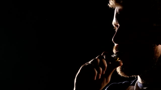 Guy smokes an electronic cigarette and exhales a lot of smoke. Black background video
