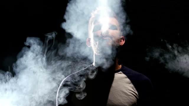 Guy smokes an electronic cigarette, enjoy the moment. Black background video