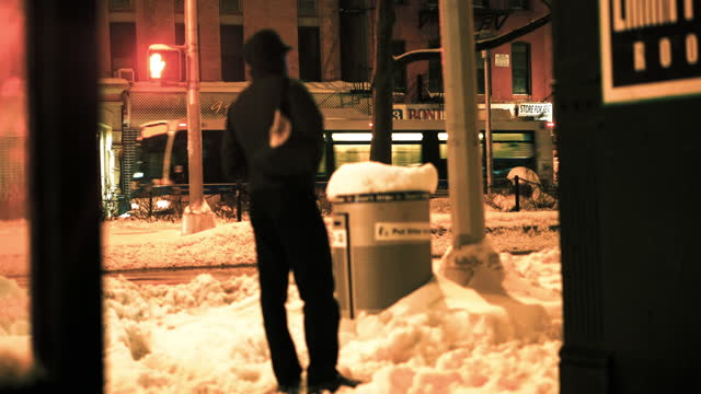 Guy standing on city block in the snow
