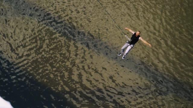 guy swings under the bridge on the safety rope - банджи джампинг стоковые видео и кадры b-roll