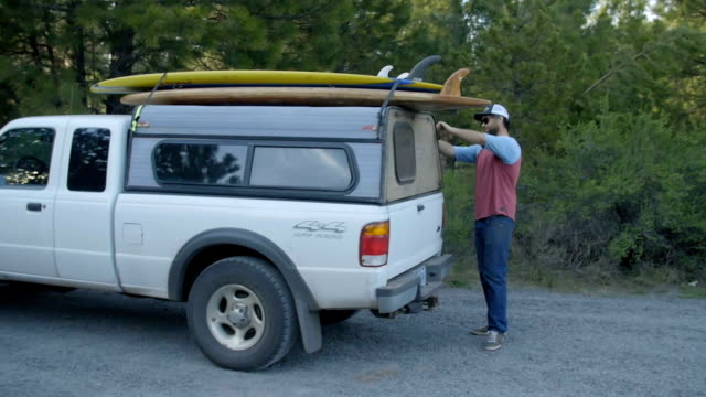 Guy takes paddleboards down from his vehicle video