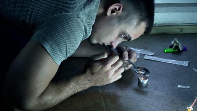 stockvideo's en b-roll-footage met een man die verslaafd aan de drugs is zit op de vloer en bereidt een dosis in een lepel op een kaars - amfetamine