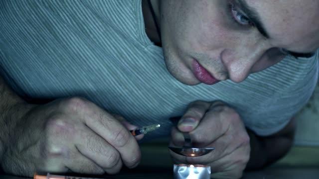stockvideo's en b-roll-footage met een man die verslaafd aan de drugs is zit op de vloer en bereidt een dosis in een lepel op een kaars. - amfetamine