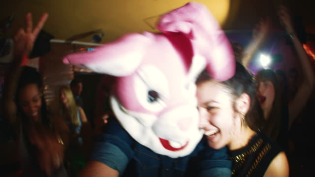 Guy with a bunny head with friends at party