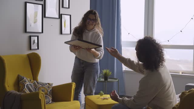 Guy with long curly hair helps young woman hang frames Guy with long curly hair helps young woman hang different frames with coloured dried leaves showing and sitting on sofa in new flat against window hanging stock videos & royalty-free footage