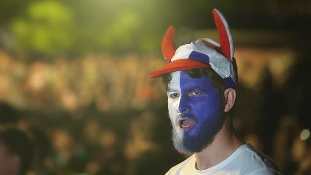 vídeos de stock e filmes b-roll de guy with painted face team flag fall asleep football stadium, yawning sport game - soccer supporter portrait