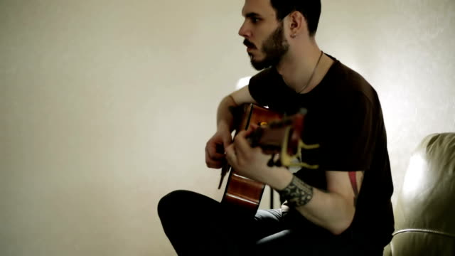 A guy with tattoos playing the guitar. video