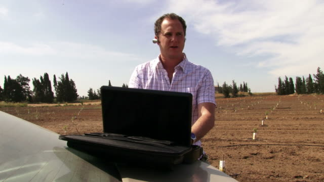 Guy working on the field with laptop video