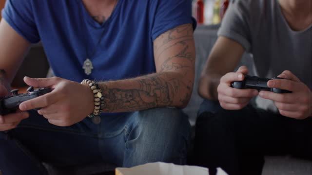 vídeos de stock e filmes b-roll de rapazes sentado no sofá jogando jogos de vídeo e a celebrar - man joystick