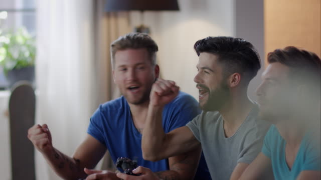 Guys sitting on couch playing video games and cheering video