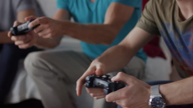 vídeos de stock e filmes b-roll de rapazes sentado no sofá jogando jogos de vídeo - criança perdida