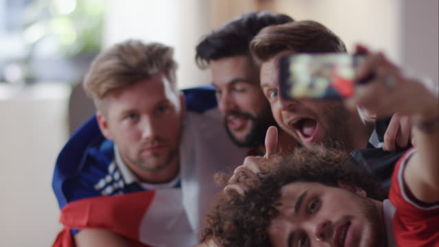 Guys sitting on couch taking selfies video