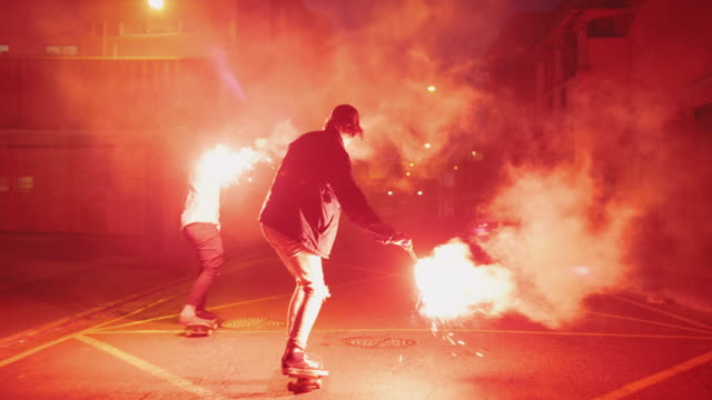 Guys skateboarding with torches on a street video