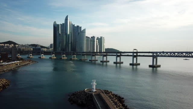 vídeos de stock e filmes b-roll de gwangan bridge and haeundae aerial view at sunrise, busan, south korea. - coreia do sul