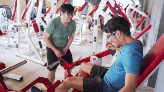 ジム事故。ジムでエクササイズマシンを使用してアジア人男性。精巣の怪我、壊れたボール - 不吉点の映像素材/bロール