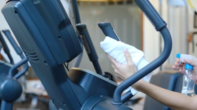 ジムの清掃と消毒。感染予防と流行の制御.スタッフは、ジムで楕円形のトレーナーをきれいにするためにワイプとアルコール消毒スプレーを使用しています。反covid-19の予防措置 - スポーツ用品点の映像素材/bロール