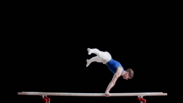 SLO MO Gymnast in balanced position on parallel bars
