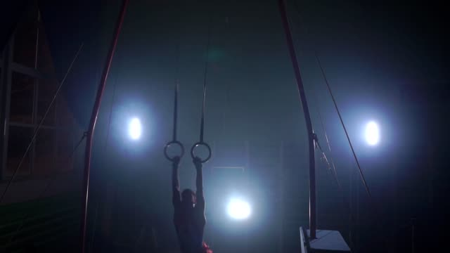 Gymnast on a dark background stands on his hands using rings in the air. Performs rotation in the Olympic program