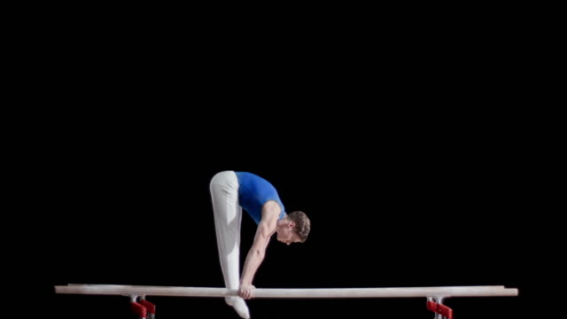 SLO MO Gymnast swinging into hand stand on parallel bars
