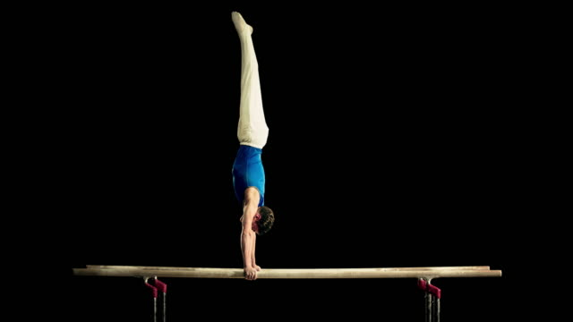 SLO MO Gymnast swinging out of handstand on parallel bars