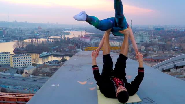 gymnastics pair performing acrobatic exercise on top of bridge, trust in partner - affidabilità video stock e b–roll