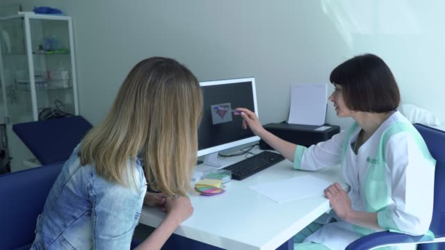 gynecologist explain patient how work her womb showing the picture on computer - ginekolog filmów i materiałów b-roll