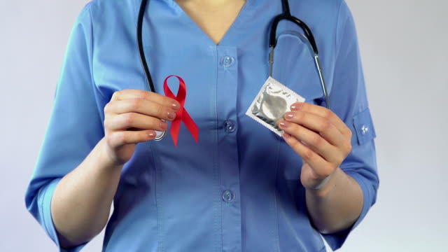Gynecologist holding red ribbon and condom, AIDS awareness, warning about video
