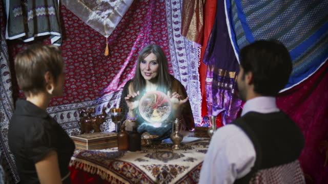 gypsy fortune teller with faulty crystal ball - mature women studio grey hair bildbanksvideor och videomaterial från bakom kulisserna