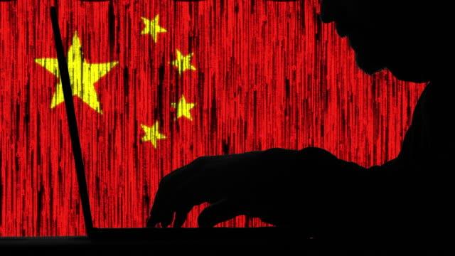 背景に中国の旗を持つ彼のラップトップ上のハッカーハッキングタイピングコード - スパイ点の映像素材/bロール