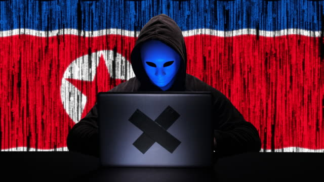 Hacker hacking typing code on his laptop with North Korea flag and binary code animation overlay in background Hacker hacking typing code on his laptop with North Korea flag and binary code animation overlay in background. The person is wearing black hoodie and is unrecognizable. The scene is situated in a studio photo/video studio environment in front of a green screen background. The footage is shot with Panasonic GH5 camera. mask disguise stock videos & royalty-free footage